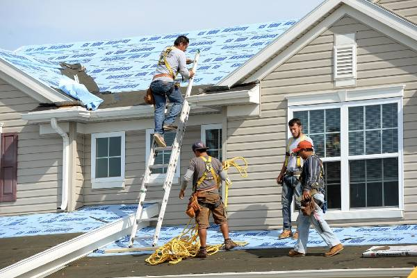 roofers on a ladder working on a shingle roof in anderson indiana